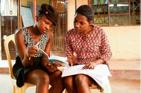 Zwei junge Frauen sehen sich Schulhefte an