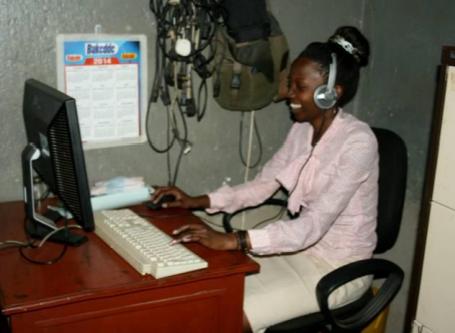Junge Frau mit Headset vor einem Computer