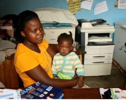 Junge Frau mit Baby vor einem Kopierer
